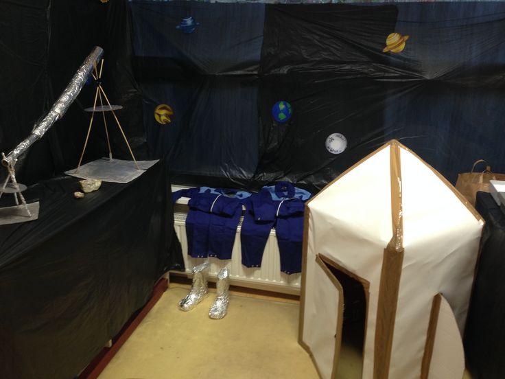Ruimtehoek met raket van kartonnendozen. Astronautpakken en laarzen. Telescoop en maanstenen.