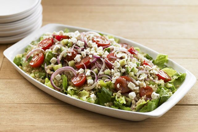 In this super side salad, quinoa is tossed with torn romaine lettuce, then gets its Mediterranean flavor from the combination of crumbled feta cheese and Greek vinaigrette dressing.