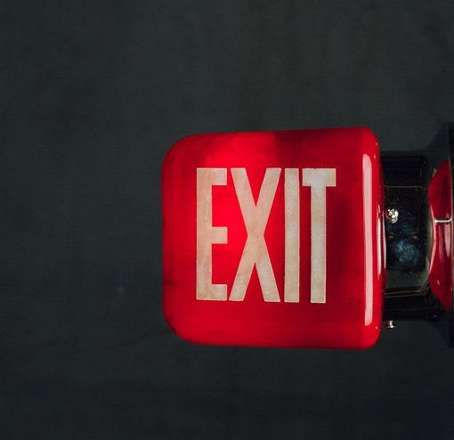 Illuminate your space with this triangle side-mount exit sign. A rich, red hue with white lettering on two sides. From the 1930s.