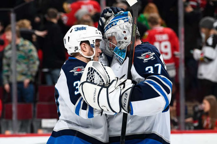 CHICAGO, IL - DECEMBER 27: Toby Enstrom #39 and goalie Connor Hellebuyck #37 of the Winnipeg Jets celebrate after defeating the Chicago Blackhawks 3-1 at the United Center on December 27, 2016 in Chicago, Illinois. (Photo by Bill Smith/NHLI via Getty Images)