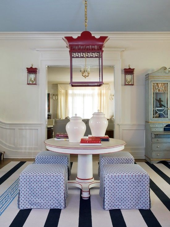 An inspiring study in detail. The strong red of the lantern-style pendant and sconces repeat in the ottoman print and pedestal table trim.