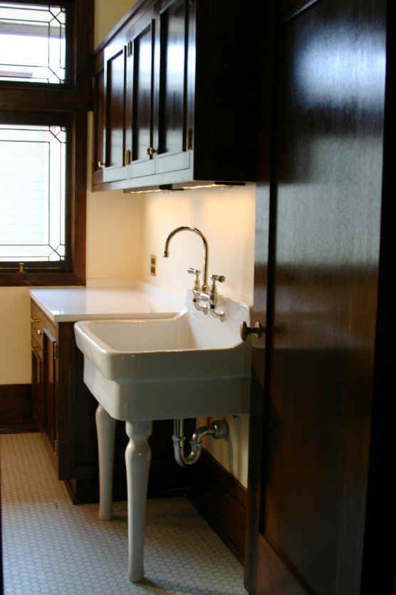 An upstairs laundry room in the Wright house.  Again, the goal was to imagine a laundry room that Wright might have designed, and to use materials that are found elsewhere to integrate the space into the rest of the house.  The sink is a contemporary utility sink that is identical to one from the early 1900's, but the porcelain legs came from a salvage source.  The cabinetry is based on the designs for the bathroom vanities, but the real key to the success of this space are the undercounter…