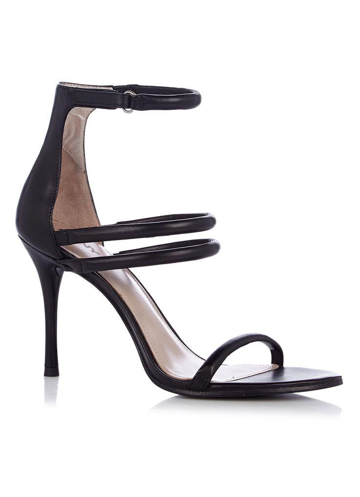 Maya sandaal van DKNY. Dit sophisticated exemplaar is uitgevoerd met een smal bandje over de voorvoet, twee bandjes over de wreef en een enkel bandje met klittenbandsluiting om de enkel. De sandaal is volledig vervaardigd uit leer.