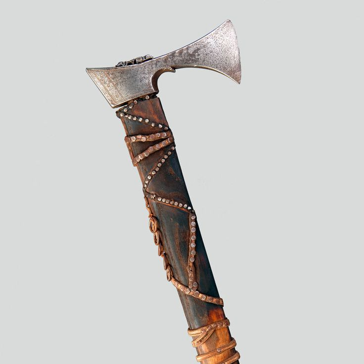 Walking stick/hatchet. Iron head, sharpened bit, stencilled ornamentation. Wooden haft, flamed, straps of leather wrapped around and nailed with numerous small nails, five attached rings.  Rajskie, P. Lesko, 1920s
