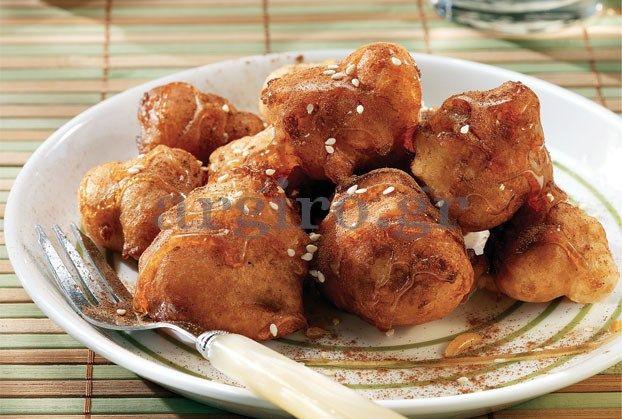 Λουκουμάδες - Loukoumades or traditional Greek doughnuts covered with honey. Lokoumades and Chalvas are the sweets we eat these days, especially on Clean Monday, when the carnival season ends and 7 weeks long fasting starts.