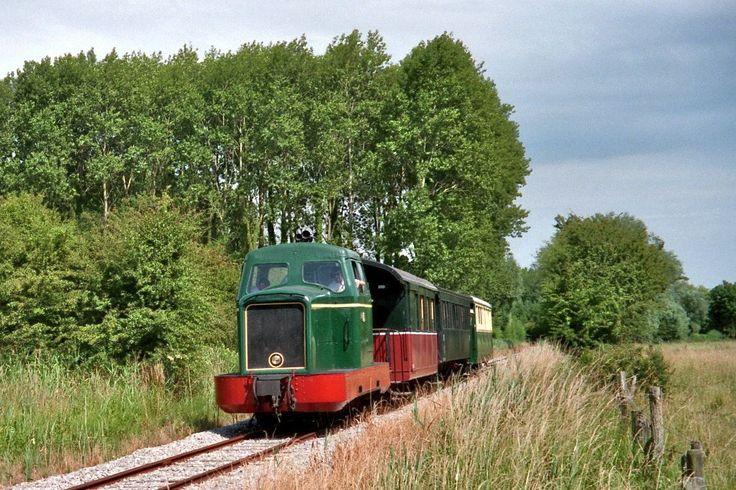 Caminhos de Ferro da Baía de Somme, departamento de Somme, região administrativa da Picardia, França. A locomotiva com seus vagões deixa a estação de  Lanchères-Pende e passa perto da aldeia de Herlicourt com destino a Cayeux-sur-Mer.  Fotografia:  P. Poschadel.