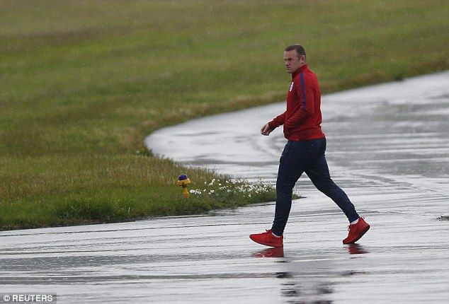 United and England captain Wayne Rooney makes his way across a rain-soaked runway on Tuesday evening