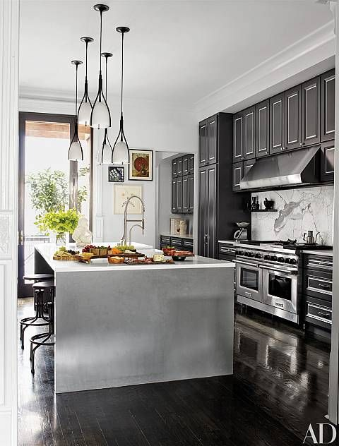 Holly Hunt Pendant Lights Are Suspended Above The Caesarstone Top Island In  The Kitchen, Which Is Equipped With A Wolf Range And Hood.