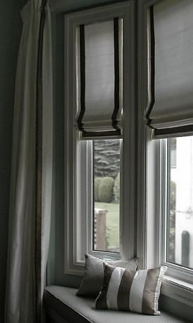 Roman shades are very well suited to tall windows. Here, they work well in a bay window space with window seat and side curtains, creating a wonderful place to curl up with your favorite book.