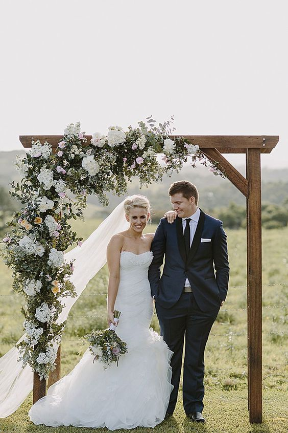 Stunning wedding arch with cascading floral arrangement in a neutral palette