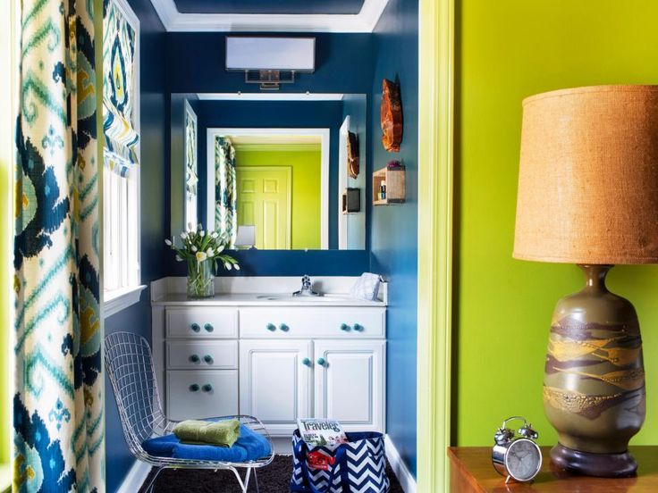 To turn the once-drab powder room into a bold and cheerful space, the walls and ceiling were painted navy blue in a semigloss finish. The dark-colored walls and ceiling help tone down the intense chartreuse paint of the adjacent guest room.