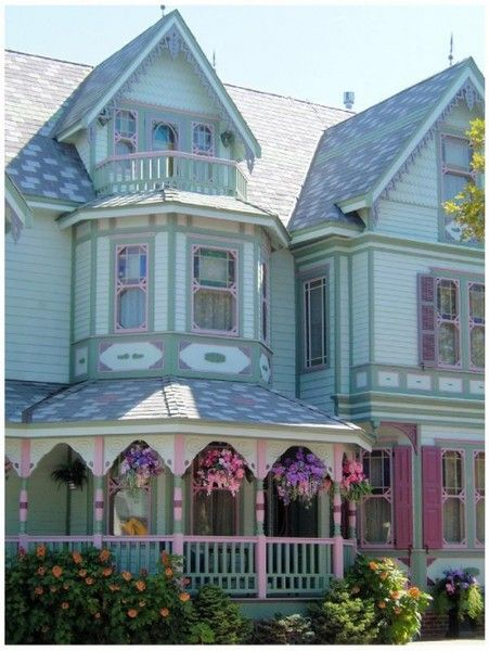 Kudos for a paint job that highlights the wonderful architectural features of this home. Altho I'd prefer some dark color to balance, the pastel look is actually kind of pretty. Flowers hanging on the porch are a bonus that sweeten the look.