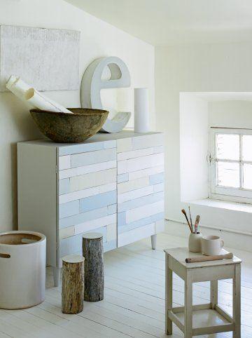 Meuble en bois dont les portes sont réalisées en morceaux de cagettes peintes en blanc