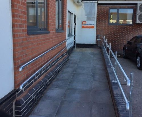 Twin rail design metal handrail system to disabled access ramp. Galvanized finish external grade rails.