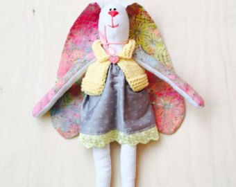 The Bunny is 100% handmade. All her clothing is either handknitted or sewed by me.  Finished Size: 41cm (16 inches) from table to top of head. Ear are about 35 cm (14 inches) Materials: linen, cotton fabrics, wool for knitwear. All pieces of clothes can be removed. You can also order customized outfit - please contact me for details!  Please contact me on any specific customised requests. Always happy to help :)  DELIVERY TIME: Estimated delivery time in the USA : 10 - 25 days Estimated…