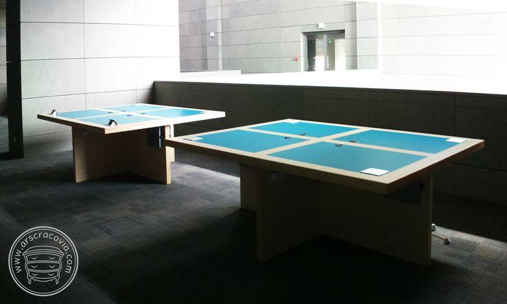 Multimedialne stoły do czytelni w bibliotece, na blatach możliwość podłączenia multimediów i oświetlenia, wykonane z kolorowych laminatów HPL i drewna.