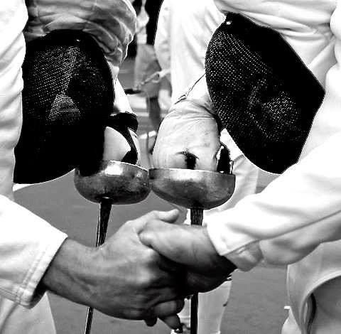 "This is called ""the fencer's handshake"", using your ungloved hand to shake at the end of a match or before switching sides on the mat."
