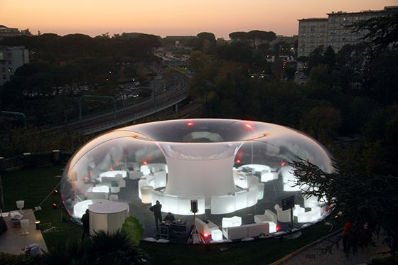 The pneumatic lounge MEDUSA is a unique venue designed for special record release events taking place at the RDS radio station headquarters in Rome. Custom made for this environment, the 18 meters wide transparent bubble provides a 250 sqm surface to be used as a multisensory space in the garden in front of the main building with light- and Sound equipment placed inside the central column of the structure.