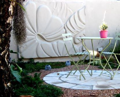A custom made,molded wall panel, becomes the understated focal point in this tiny garden