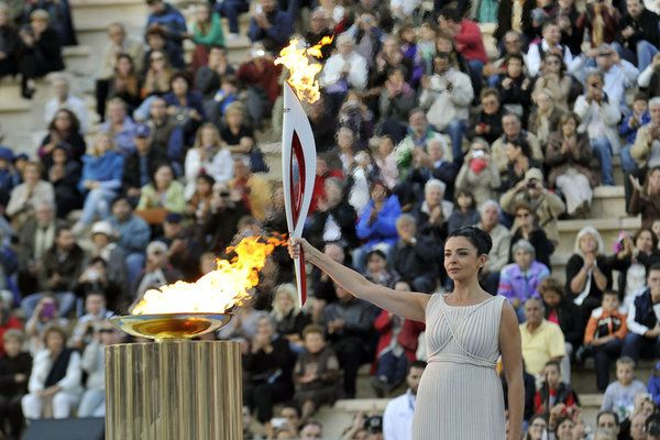ATHENS, GREECE - OCTOBER 05: A woman holds the Olympic Flame during the Olympic Torch Handover Ceremony, on October 05, 2013 in Athens, Greece. (Photo by Michalis Karagiannis/Getty Images)
