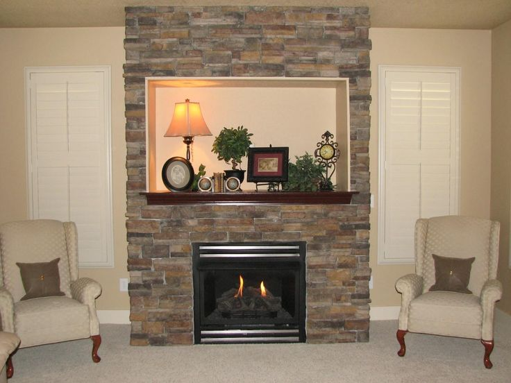 delightful living room design with two grey sofas and insert gas fireplace with faux stone fireplace and decorative fire mantel with desk lamp and pictures