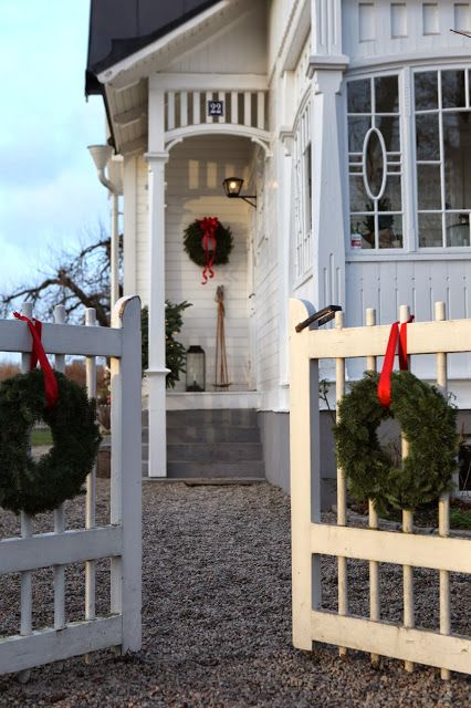 Beautiful white cottage and gate trimmed w/ greens and red ribbon - traditional always works!