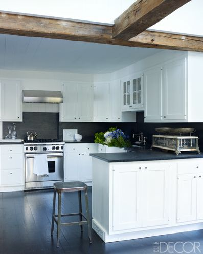 Low ceiling kitchen adjacent to beamed ceiling