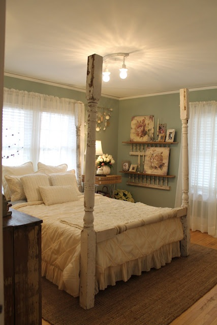 a sweet cottage bedroom, complete with a bed made from porch posts.  Like the ladder shelves on the wall too.