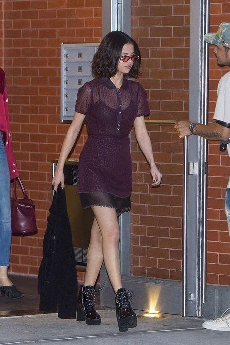 Selena Gomez In a sheer purple dress over a black slip, platform leather boots, and red-tinted sunglasses while out in New York. #fashion #style #outfit #celebrity #dress #hair #selenagomez