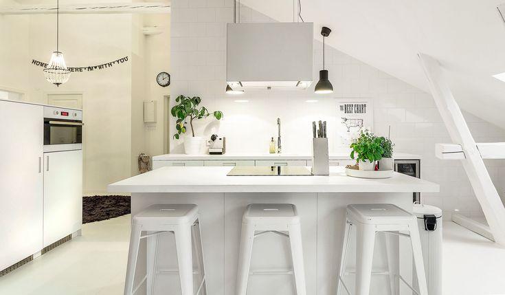 Ska man göra ett vitt kök kan man lika gärna gå hela vägen. Här har manskapat en vit dröm med några få kontrastdetaljer.