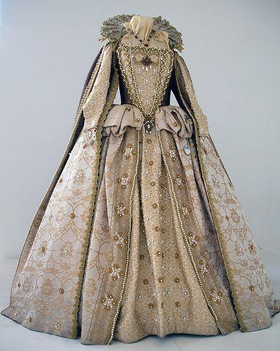 Ricco abito in seta e damasco, con ricami ed applicazioni di passamanerie in filo d'oro. Il colletto in chiffon è rigido. Costo £580