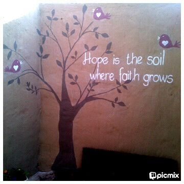 """""""Hope is the soil where faith grows"""" quote and tree with pink birds painted on courtyard wall."""