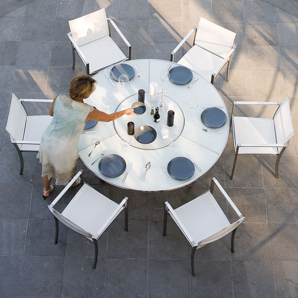 The Beautifully Designed Outdoor Dining Table Has A White Glass Top With Built