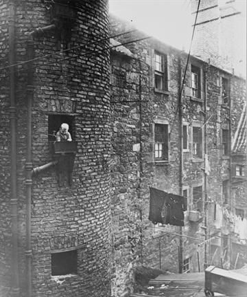 Back Court of Glasgow tenement in 1930's No play areas for children, note the 'fresh air cages' constructed outside windows ! Different times !