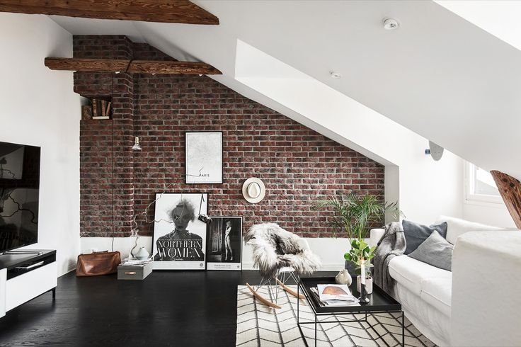 The exposed brick wall is accentuated by the sleek modern walls and furniture for a perfect blend of styles
