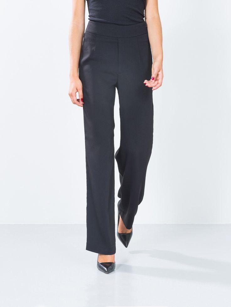Bukser med høy midje og vide ben. Buksen er laget i et pent fallende stoff, og har glidelås i siden.   Sort
