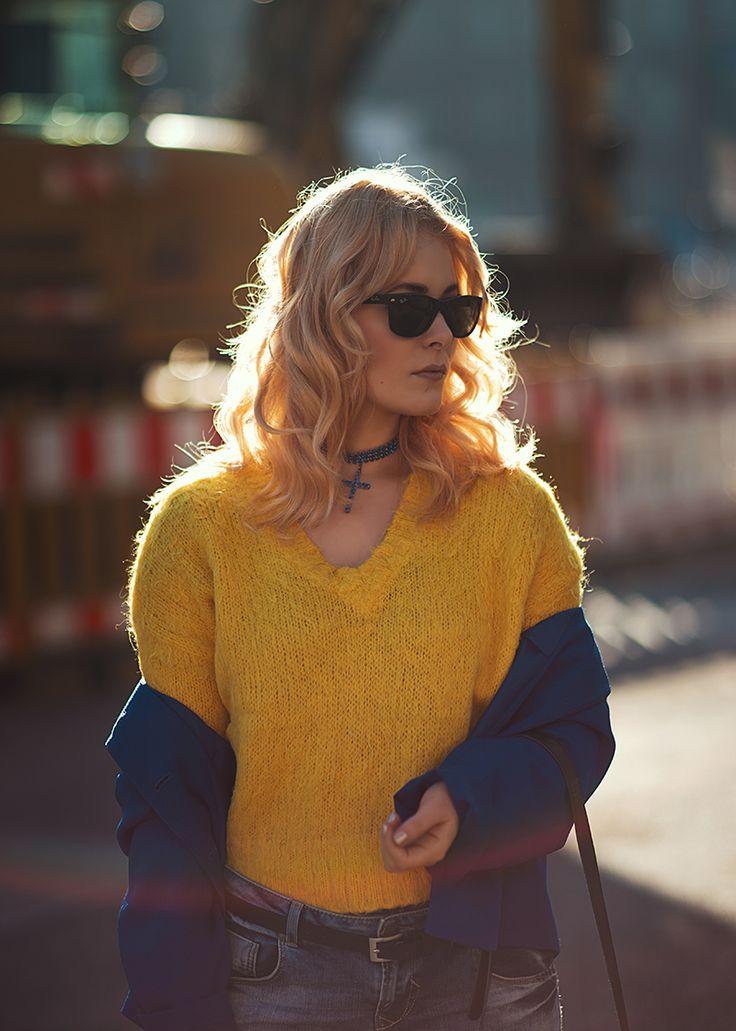 Streetstyle mit gelbem Pullover und royalblauer Jacke zur Jeans