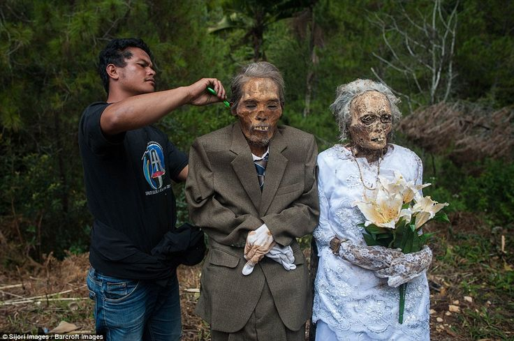 ma'nene festival in indonesia ~ dug up their grandparents and dress them with new clothes to show their love.