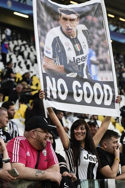 A supporter of Juventus holds a poster of Juventus' forward from Croatia Mario Mandzukic   before the UEFA Champions League quarter final first leg football match Juventus vs Barcelona, on April 11, 2017 at the Juventus stadium in Turin.  / AFP PHOTO / Miguel MEDINA