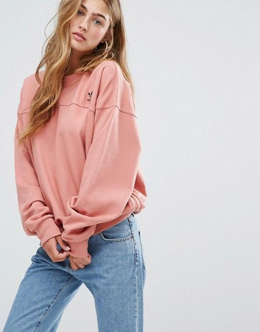 Oversized pink Adidas sweatshirt paired with washed blue jeans