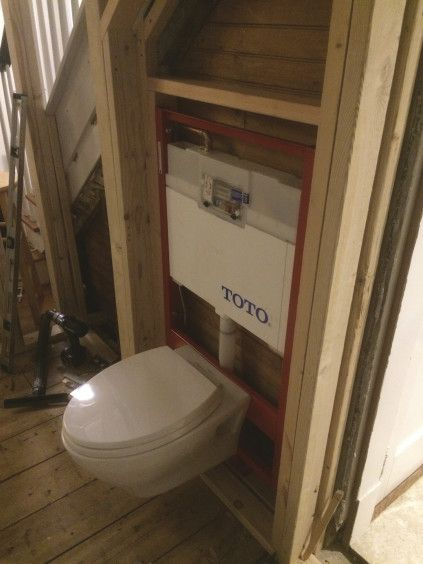 Even with the framing on the flat, extra space was needed for code-required clearance for the wall-hung toilet. The framing was recessed as far as possible below the stairway. Here the tank is installed and the toilet hung in place temporarily.