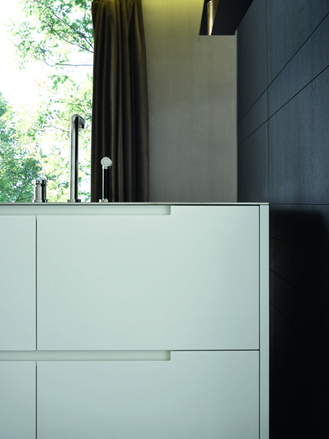 """Varenna_PHOENIX_A detail of the base units with the distinguishing handle profile of model Phoenix. Doors in glacier white embossed lacquered finishing, personalised steel worktop Varenna by Barazza thickness 1/4""""."""