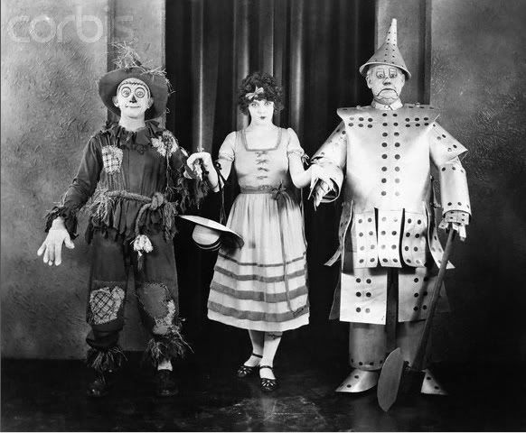 Cast members of the 1925 silent film version of The Wizard of Oz. Larry Semon as the Scarecrow, Dorothy Dwan as Dorothy and Oliver Hardy as the Tin Woodsman.