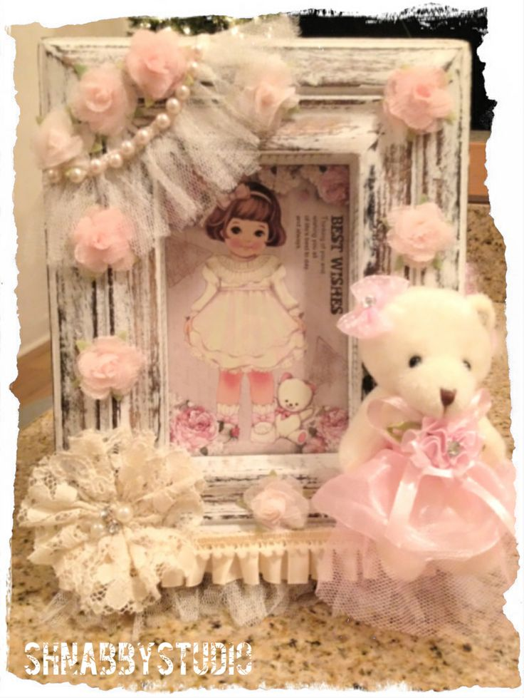 This beautifully feminine, shabby chic photo frame would make a perfect gift for a new baby or little girl's room! Ruffle edged, distressed wood with lace and ribbon flowers give a great mix of textures for interest. A pink dressed teddy bear adds extra dimension and adds a wonderfully sweet and child-like look. Frame a vintage children's book illustration or baby photo for the picture. This is so cute!