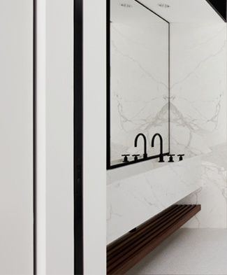 Marble trough sink, marble wall in black + white bathroom
