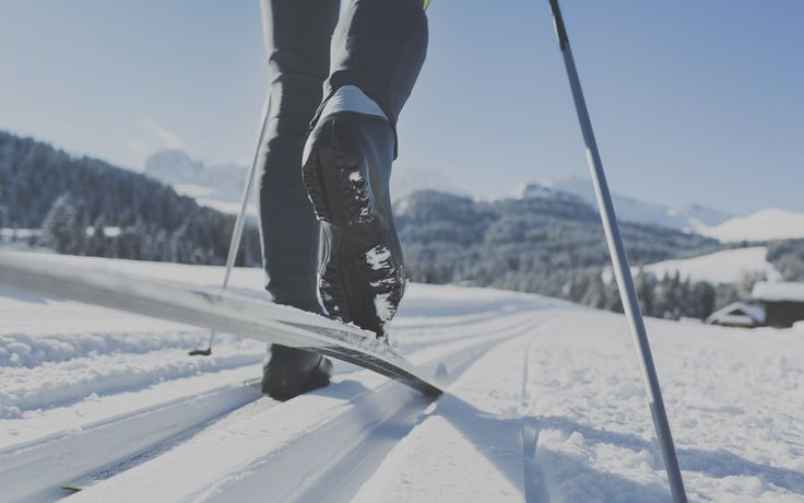 Feet with cross-country skis walk across a snowy landscape