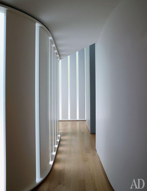 Белые жалюзи рассеивают свет в коридоре, ведущем в спальни.