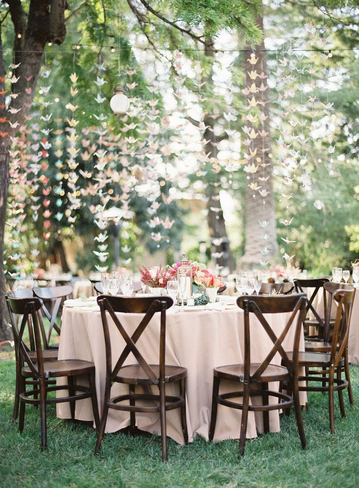 Dangle paper cranes from tree branches for an outdoor party.
