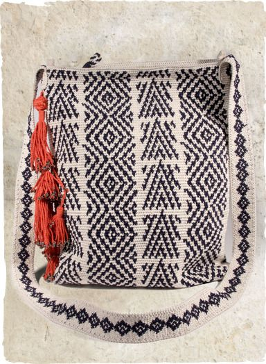 The extraordinary #pima bag, #handcrocheted in navy and cream kilim motifs and embellished with cherry-red, beaded tassels. Finished with two inside pockets and full lining.