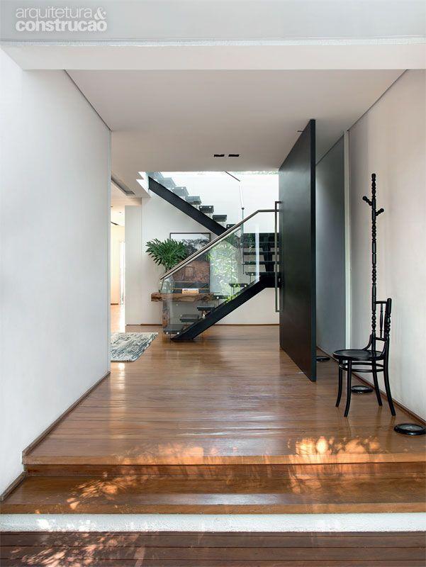 Escada em U, degraus de ipê-rosa ebanizado, guarda-corpo de vidro temperado 12 mm e corrimão de aço inox escovado. Projeto de FGMF Arquitetos.